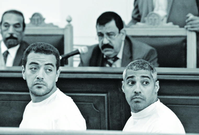 Cameraman Baher Mohamed, left, and Mohamed Fadel Fahmy, the Cairo bureau chief for al Jazeera English, look at reporters sitting behind them Monday, March 31, 2014, as Judge Mohamed Nagy listens to the defendants' complaints about the conditions they are being held in. Three Al Jazeera journalists, including Australian Peter Greste (not pictured) are standing trial on terror charges. (Amina Ismail/MCT)