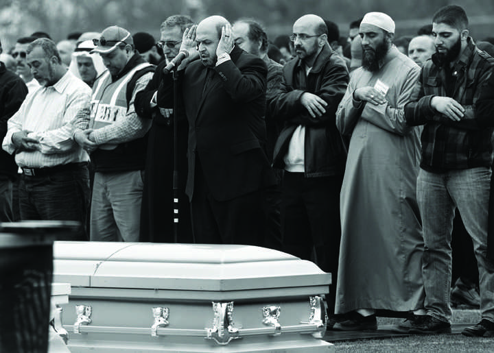 Dr. Mohammad Abu-Salha, center, leads mourners in prayer over the caskets of his daughters Yusor Abu-Salha, 21,and Razan Abu-Salha, 19, and Yusor's husband Deah Barakat, 23, during a funeral service at the Method Road Soccer Complex on Feb. 12, 2015 on N.C. State's campus in Raleigh, N.C. Officials say that 5,500 people attend the event for the 3 young Muslims who were shot and killed in Chapel Hill on Tuesday night. (Corey Lewenstein/News & Observer/TNS)
