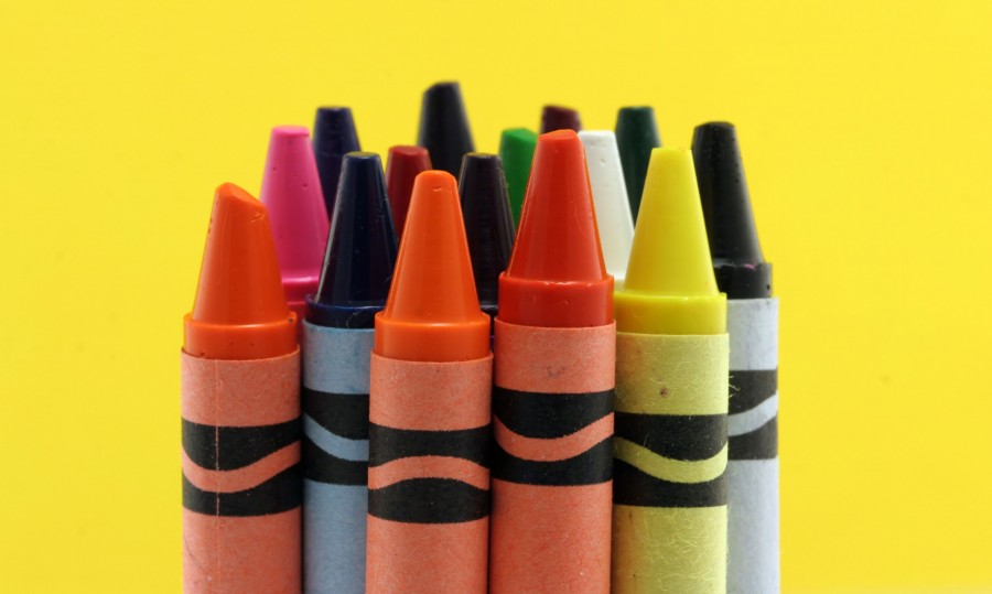 Group of new crayons isolated against a yellow background.