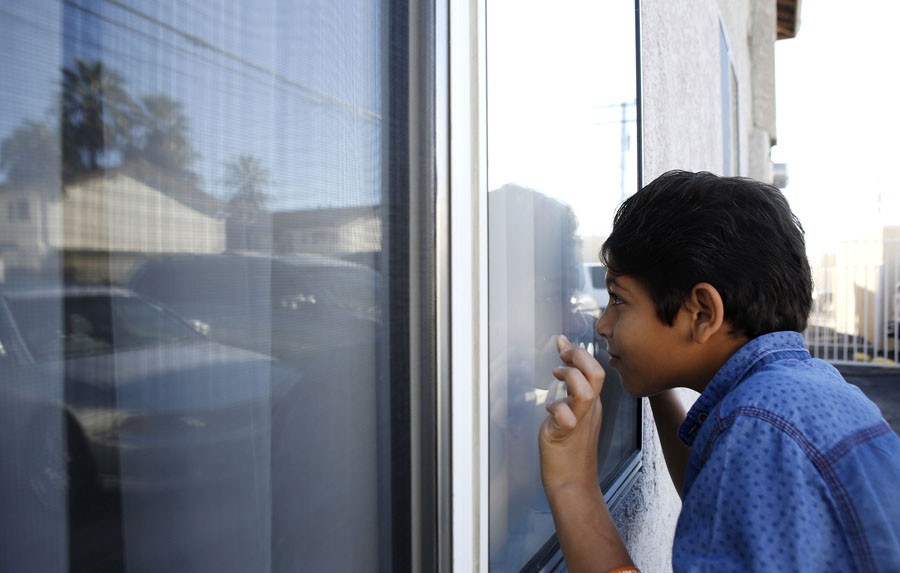 Omran Waiweh, 12, looks into his family's new apartment as he tries to get their attention to help unload the truck of donated furniture and start moving into their new place on Nov. 23, 2015 in Pomona, Calif. (Katie Falkenberg/Los Angeles Times/TNS)