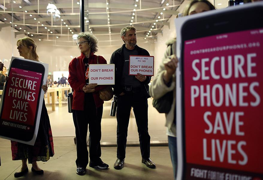 Protesters, from left, Sandra Bell, Victoria Best, and Charles Fredricks, hold signs in support of Apple store in Santa Monica, Calif., on Tuesday, Feb. 23, 2016. Rallies were planned at Apple stores across the country to support the company's refusal to help the FBI access the cell phone of a gunman who took part in the killings of 14 people at the Inland Regional Center in San Bernardino. (Katie Falkenberg/Los Angeles Times/TNS)