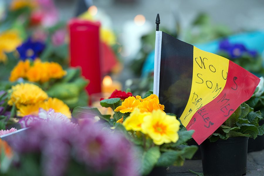 ''Nous sommes Bruxelles'' (We are Brussels) is written on a small Belgian flag next to flowers and candles outside the stock exchange at Place de la Bourse in Brussels on Tuesday, March 22, 2016. (Federico Gambarini/DPA/Zuma Press/TNS)