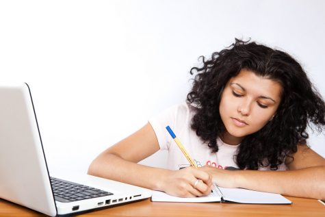 Student at their laptop working on an assignment and taking notes